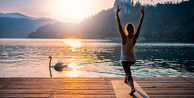 person doing yoga by lake