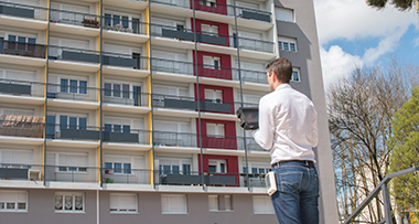 man using mobile reader outside building