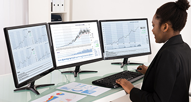 woman working on three monitors